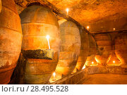 Купить «Antique winery in Spain with clay vessels terracotta amphora  pots Mediterranean tradition with candlelight», фото № 28495528, снято 10 октября 2013 г. (c) Ingram Publishing / Фотобанк Лори