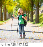 Купить «Blond explorer kid girl walking with backpack hiking in autumn trees track holding stick», фото № 28497152, снято 5 октября 2013 г. (c) Ingram Publishing / Фотобанк Лори