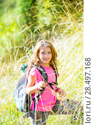 Купить «Explorer kid girl walking with backpack between forest grass», фото № 28497168, снято 5 октября 2013 г. (c) Ingram Publishing / Фотобанк Лори