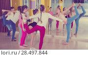 Купить «Teenagers with choreographer doing leg-split and crab position», фото № 28497844, снято 3 марта 2018 г. (c) Яков Филимонов / Фотобанк Лори