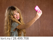 Купить «Blond kid girl taking pictures with mobile smartphone portrait on vintage background», фото № 28499708, снято 9 февраля 2014 г. (c) Ingram Publishing / Фотобанк Лори