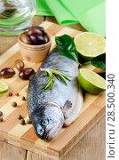 Купить «Raw trout on the chopping board with limes», фото № 28500340, снято 20 марта 2013 г. (c) Ingram Publishing / Фотобанк Лори