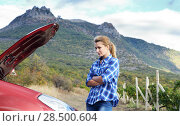 Young woman near broken car needs assistance looking under opened hood. Car insurance concept. Стоковое фото, фотограф Olena Mykhaylova / Ingram Publishing / Фотобанк Лори
