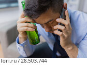man with bottle of alcohol calling on smartphone. Стоковое фото, фотограф Syda Productions / Фотобанк Лори