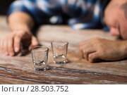Купить «drunk man with empty glasses on table at night», фото № 28503752, снято 24 ноября 2017 г. (c) Syda Productions / Фотобанк Лори