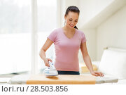 Купить «woman or housewife ironing towel by iron at home», фото № 28503856, снято 29 апреля 2018 г. (c) Syda Productions / Фотобанк Лори