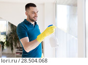 Купить «man in rubber gloves cleaning window with spray», фото № 28504068, снято 10 мая 2018 г. (c) Syda Productions / Фотобанк Лори