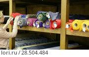 Купить «Young woman looking for interesting cloth in textile shop», видеоролик № 28504484, снято 28 марта 2018 г. (c) Яков Филимонов / Фотобанк Лори
