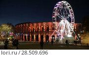 Купить «Spinning ferris wheel near illuminated Arena of Nimes, France», видеоролик № 28509696, снято 1 декабря 2017 г. (c) Яков Филимонов / Фотобанк Лори