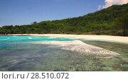 Купить «Small waves and white beach at Seychelles islands. La Digue, Anse Cocos», видеоролик № 28510072, снято 2 июня 2018 г. (c) Mikhail Starodubov / Фотобанк Лори