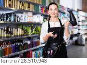 Купить «Young female hairdresser holding blow dryer and hair cutters in shop», фото № 28510948, снято 31 марта 2018 г. (c) Яков Филимонов / Фотобанк Лори