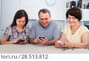 Купить «senior parents and daughter with smartphones», фото № 28513812, снято 20 января 2020 г. (c) Яков Филимонов / Фотобанк Лори