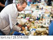 Купить «Positive elderly man choosing interesting souvenirs at traditional flea market», фото № 28514008, снято 23 октября 2017 г. (c) Яков Филимонов / Фотобанк Лори