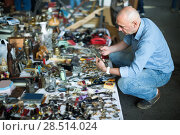 Купить «adult man looking for vintage goods at flea market», фото № 28514024, снято 23 октября 2017 г. (c) Яков Филимонов / Фотобанк Лори