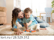 Купить «cute little boy and babysitter playing with toy by the home», фото № 28529312, снято 20 сентября 2018 г. (c) Оксана Кузьмина / Фотобанк Лори