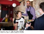 Купить «Waiter bringing salads to guests», фото № 28529936, снято 18 декабря 2017 г. (c) Яков Филимонов / Фотобанк Лори