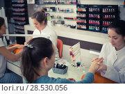 Купить «Nail technicians performing manicure», фото № 28530056, снято 28 апреля 2017 г. (c) Яков Филимонов / Фотобанк Лори