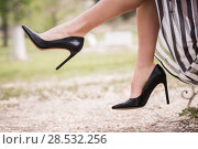 Black high heels on the feet of a young woman in a park. Стоковое фото, фотограф Javier Sánchez Mingorance / Ingram Publishing / Фотобанк Лори