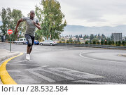Купить «Black man running outdoors in urban road listening to music with white headphones. Young male exercising with city scape at the background.», фото № 28532584, снято 20 ноября 2016 г. (c) Ingram Publishing / Фотобанк Лори
