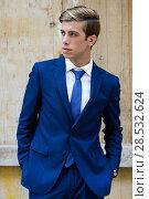 Купить «Portrait of an attractive young businessman in urban background wearing blue suit a necktie. Blonde hair», фото № 28532624, снято 17 сентября 2013 г. (c) Ingram Publishing / Фотобанк Лори