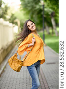 Купить «Young woman with moving hair wearing casual clothes and modern bag in urban background. Happy girl with wavy hairstyle in the wind.», фото № 28532632, снято 30 апреля 2017 г. (c) Ingram Publishing / Фотобанк Лори