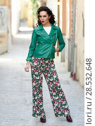 Купить «Young brunette woman, model of fashion, wearing green modern jacket and flower pants. Pretty caucasian girl with long wavy hairstyle. Female with red lips in urban background.», фото № 28532648, снято 11 марта 2017 г. (c) Ingram Publishing / Фотобанк Лори