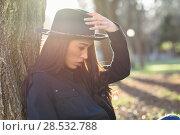 Купить «Portrait of thoughtful woman sitting alone outdoors wearing hat. Nice backlit with sunlight», фото № 28532788, снято 12 января 2016 г. (c) Ingram Publishing / Фотобанк Лори