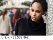 Купить «Young black female standing in an urban street. Mixed woman wearing poloneck sweater and skirt.», фото № 28532868, снято 10 декабря 2016 г. (c) Ingram Publishing / Фотобанк Лори