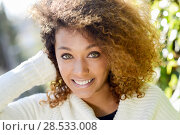 Beautiful young African American woman with afro hairstyle and green eyes wearing white winter dress with autumn leaves in the background. Стоковое фото, фотограф Javier Sánchez Mingorance / Ingram Publishing / Фотобанк Лори