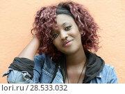 Купить «Portrait of beautiful black woman in urban background with red hair», фото № 28533032, снято 16 марта 2013 г. (c) Ingram Publishing / Фотобанк Лори