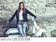 Woman in urban background smiling and wearing casual clothes with a old scooter in the background. Стоковое фото, фотограф Javier Sánchez Mingorance / Ingram Publishing / Фотобанк Лори