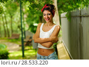 Купить «Portrait of a pin-up girl. American style, in a garden, wearing jeans and t-shirt», фото № 28533220, снято 20 мая 2012 г. (c) Ingram Publishing / Фотобанк Лори