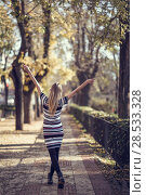 Young blonde woman walking in the street raising her arms. Beautiful girl in urban background wearing striped dress and black tights. Female with straight hair. Back view. Стоковое фото, фотограф Javier Sánchez Mingorance / Ingram Publishing / Фотобанк Лори
