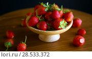 Купить «Ripe red organic strawberry on a wooden table», видеоролик № 28533372, снято 6 июня 2018 г. (c) Peredniankina / Фотобанк Лори