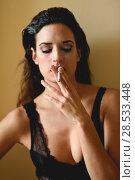 Купить «Young woman in black lingerie smoking cigarette», фото № 28533448, снято 28 ноября 2017 г. (c) Ingram Publishing / Фотобанк Лори
