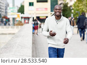 Купить «Black young man with a smartphone in his hand in urban background. Young african guy with shaved head wearing casual clothes and white headphones.», фото № 28533540, снято 20 ноября 2016 г. (c) Ingram Publishing / Фотобанк Лори
