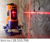 Купить «Laser measurement level for construction works, small depth of sharpness», фото № 28533708, снято 6 марта 2016 г. (c) Куликов Константин / Фотобанк Лори