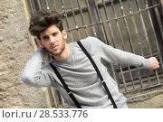 Купить «Portrait of young man wearing suspenders in urban background», фото № 28533776, снято 8 апреля 2014 г. (c) Ingram Publishing / Фотобанк Лори