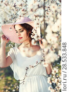 Купить «Portrait of young woman in the flowered field in the spring time. Almond flowers blossoms. Girl wearing white dress and pink sun hat», фото № 28533848, снято 10 марта 2015 г. (c) Ingram Publishing / Фотобанк Лори