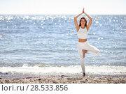 Купить «Young woman doing yoga in the beach. Female wearing white sport clothes in tree asana with defocused sea background.», фото № 28533856, снято 29 марта 2017 г. (c) Ingram Publishing / Фотобанк Лори