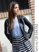 Купить «Portrait of young woman smiling in urban background wearing casual clothes. Girl wearing striped skirt, sweater and leather jacket», фото № 28534032, снято 14 апреля 2015 г. (c) Ingram Publishing / Фотобанк Лори