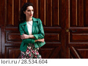 Купить «Young brunette woman, model of fashion, wearing green modern jacket and flower pants. Pretty caucasian girl with long wavy hairstyle. Female with red lips in urban background.», фото № 28534604, снято 11 марта 2017 г. (c) Ingram Publishing / Фотобанк Лори