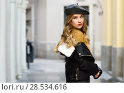 Купить «Blonde russian woman in urban background. Beautiful young girl wearing beret, black leather jacket and mini skirt standing in the street. Pretty female with long wavy hair hairstyle and blue eyes.», фото № 28534616, снято 24 января 2017 г. (c) Ingram Publishing / Фотобанк Лори