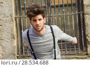 Купить «Portrait of young man wearing suspenders in urban background», фото № 28534688, снято 8 апреля 2014 г. (c) Ingram Publishing / Фотобанк Лори
