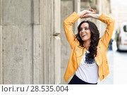 Купить «Young brunette woman, model of fashion, wearing orange modern jacket and blue skirt. Pretty caucasian girl with long wavy hairstyle smiling. Female raising her arms in urban background.», фото № 28535004, снято 11 марта 2017 г. (c) Ingram Publishing / Фотобанк Лори