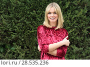 Купить «Beautiful blonde woman in green leaves background. Young girl wearing red dress standing in the street. Pretty female with frizzy hairstyle and blue eyes.», фото № 28535236, снято 22 января 2017 г. (c) Ingram Publishing / Фотобанк Лори