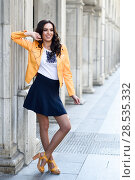 Young brunette woman, model of fashion, wearing orange modern jacket and blue skirt. Pretty caucasian girl with long wavy hairstyle smiling. Female raising her arms in urban background. Стоковое фото, фотограф Javier Sánchez Mingorance / Ingram Publishing / Фотобанк Лори
