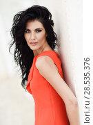 Купить «Brunette woman, model of fashion, wearing orange short dress. Young girl with curly hairstyle in an urban street», фото № 28535376, снято 7 июля 2016 г. (c) Ingram Publishing / Фотобанк Лори