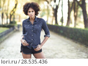 Купить «Young black woman with afro hairstyle standing in urban background. Mixed woman wearing blue shirt and shorts.», фото № 28535436, снято 10 декабря 2016 г. (c) Ingram Publishing / Фотобанк Лори