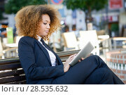 Купить «Beautiful black woman using tablet computer in urban background. Businesswoman wearing suit with trousers and tie, afro hairstyle.», фото № 28535632, снято 25 ноября 2015 г. (c) Ingram Publishing / Фотобанк Лори